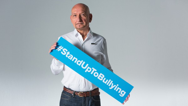 Sir Ben Kingsley holding a  Stand Up To Bullying Day banner